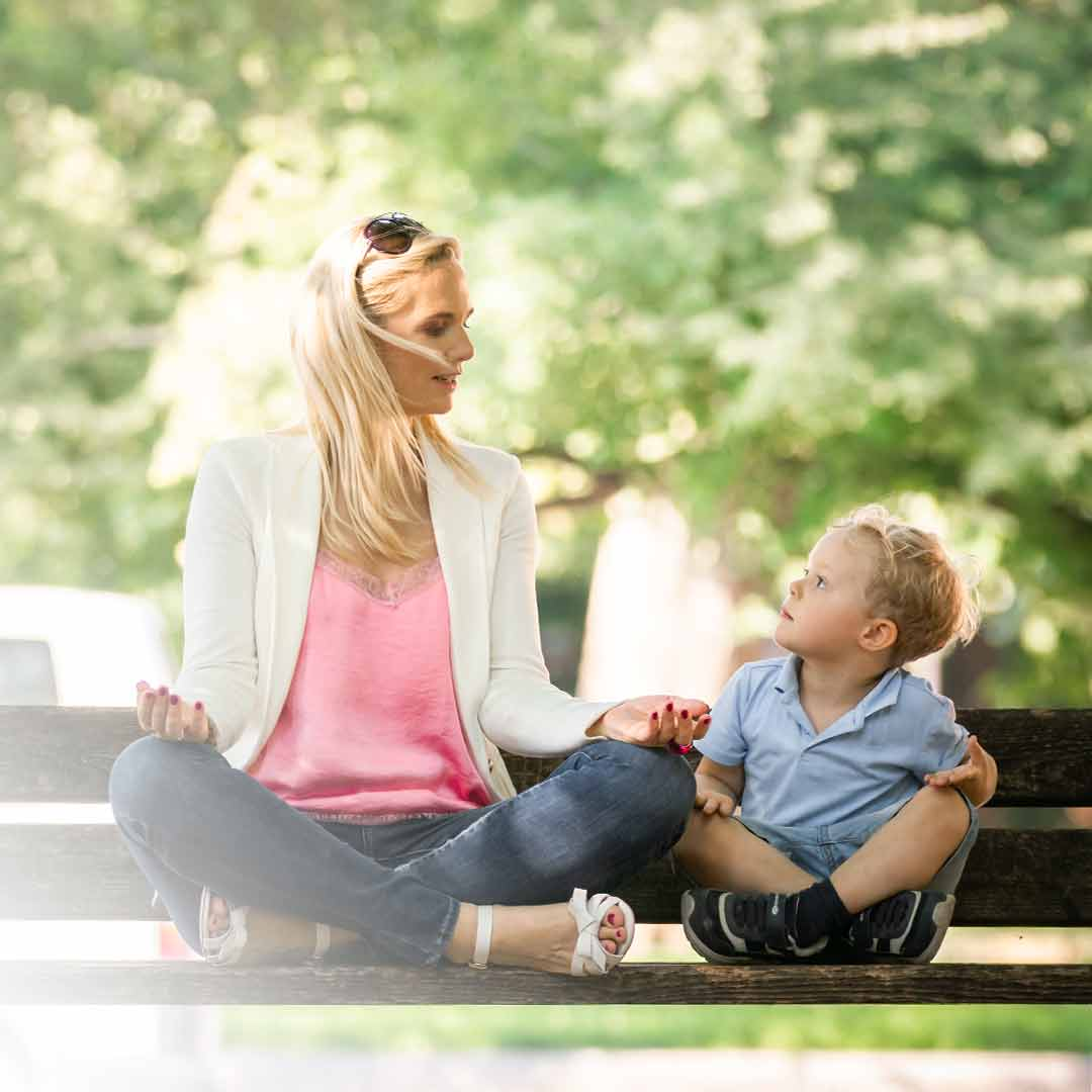 Julia sitzt zusammen mit ihrem Sohn auf einer Bank